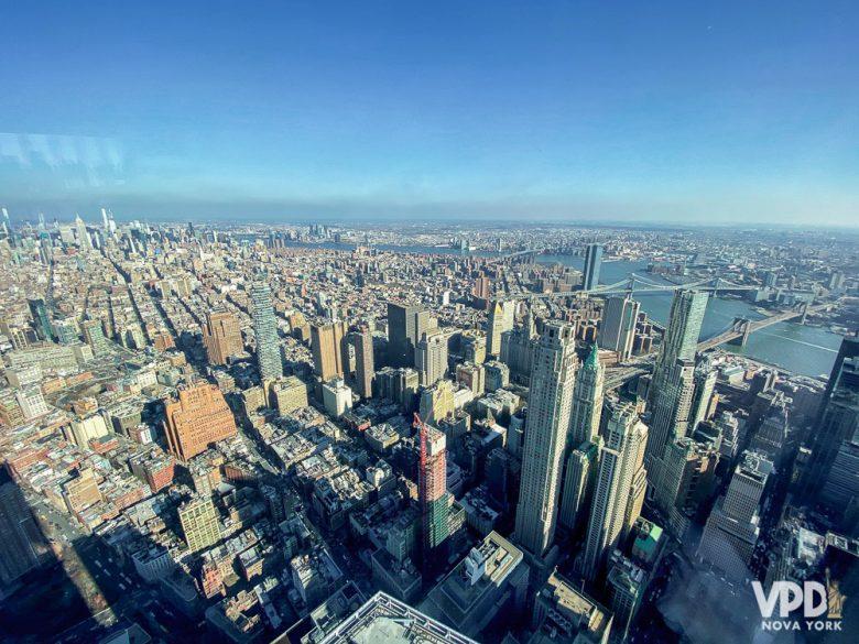 Foto da cidade de Nova York vista de cima, com o céu azul ao fundo