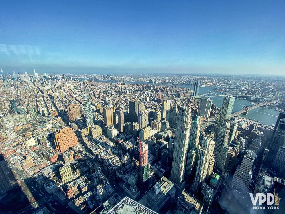 Foto de Nova York vista de cima, com os edifícios altos e o céu azul ao fundo. Conheça o VPD NY para dicas sobre a cidade.
