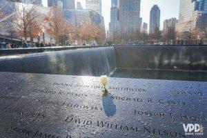 Foto de uma flor em cima de uma das placas com o nome das vítimas no Memorial do 11 de Setembro, em Nova York