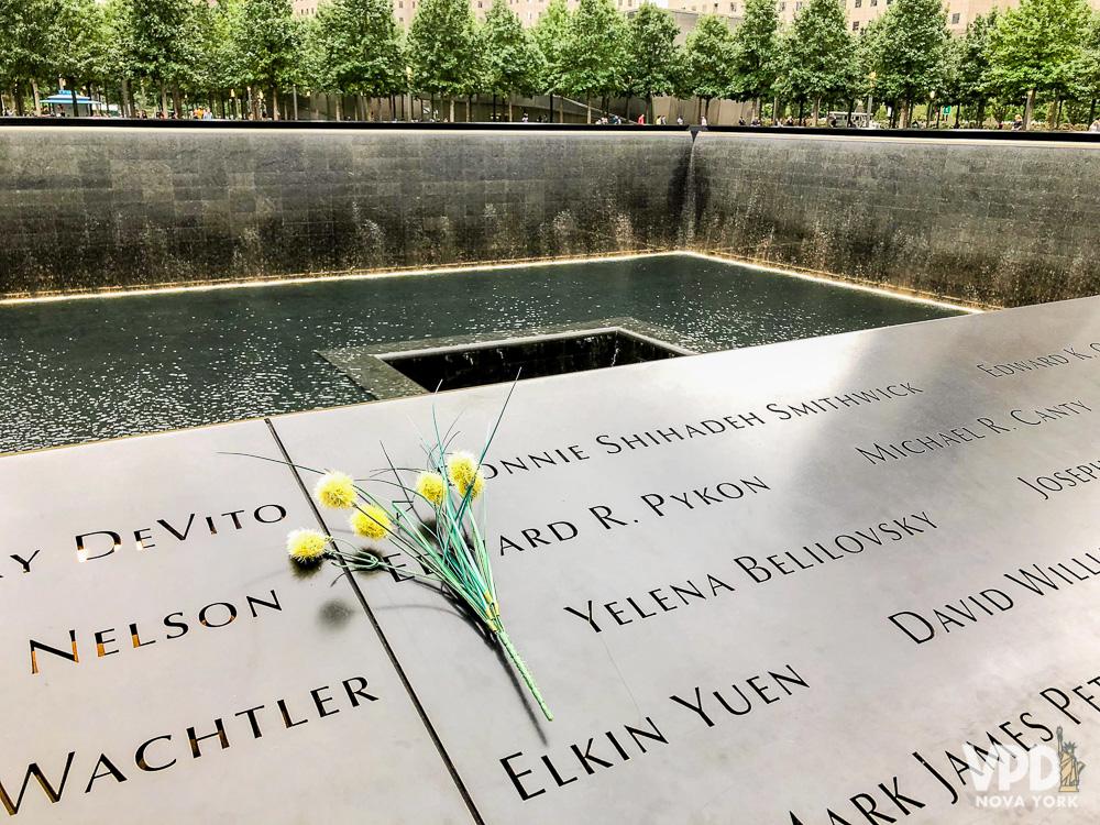 Foto de uma flor sobre uma das placas homenageando as vítimas no Memorial do 11 de Setembro em Nova York