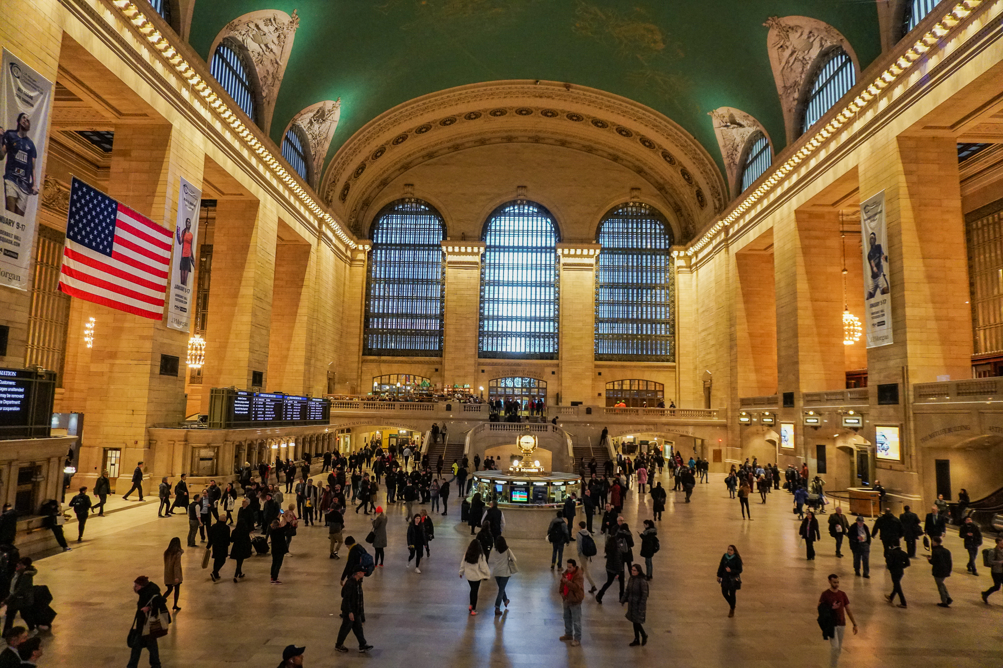 Foto do interior da estação Grand Central, em Nova York, com a cúpula alta pintada de verde e visitantes circulando