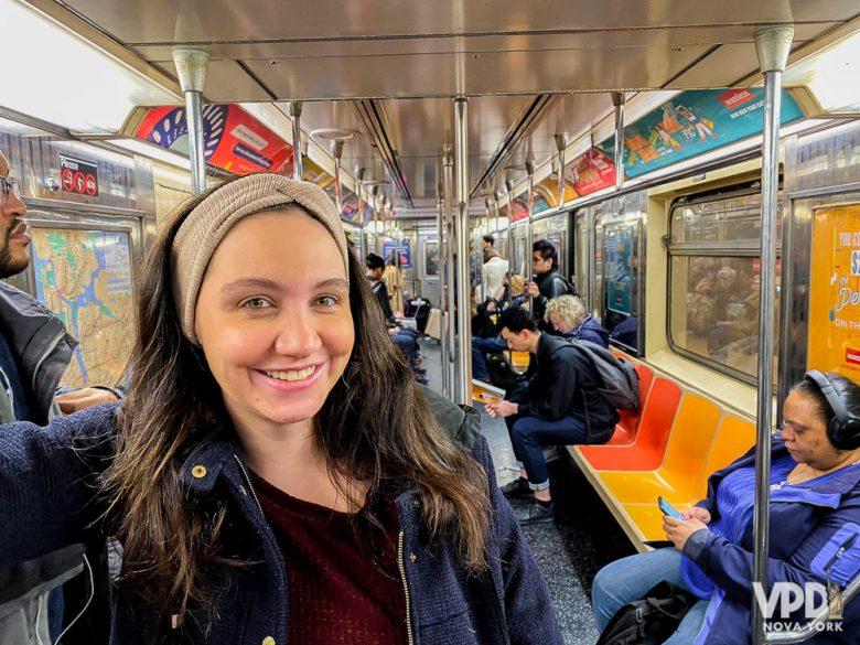 Foto da Rê sorrindo, em pé dentro do trem do metrô de NY