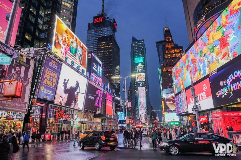 Várias linhas do metrô param na Time Square. Foto da Times Square iluminada e cheia ao entardecer, com os prédios de Nova York ao fundo