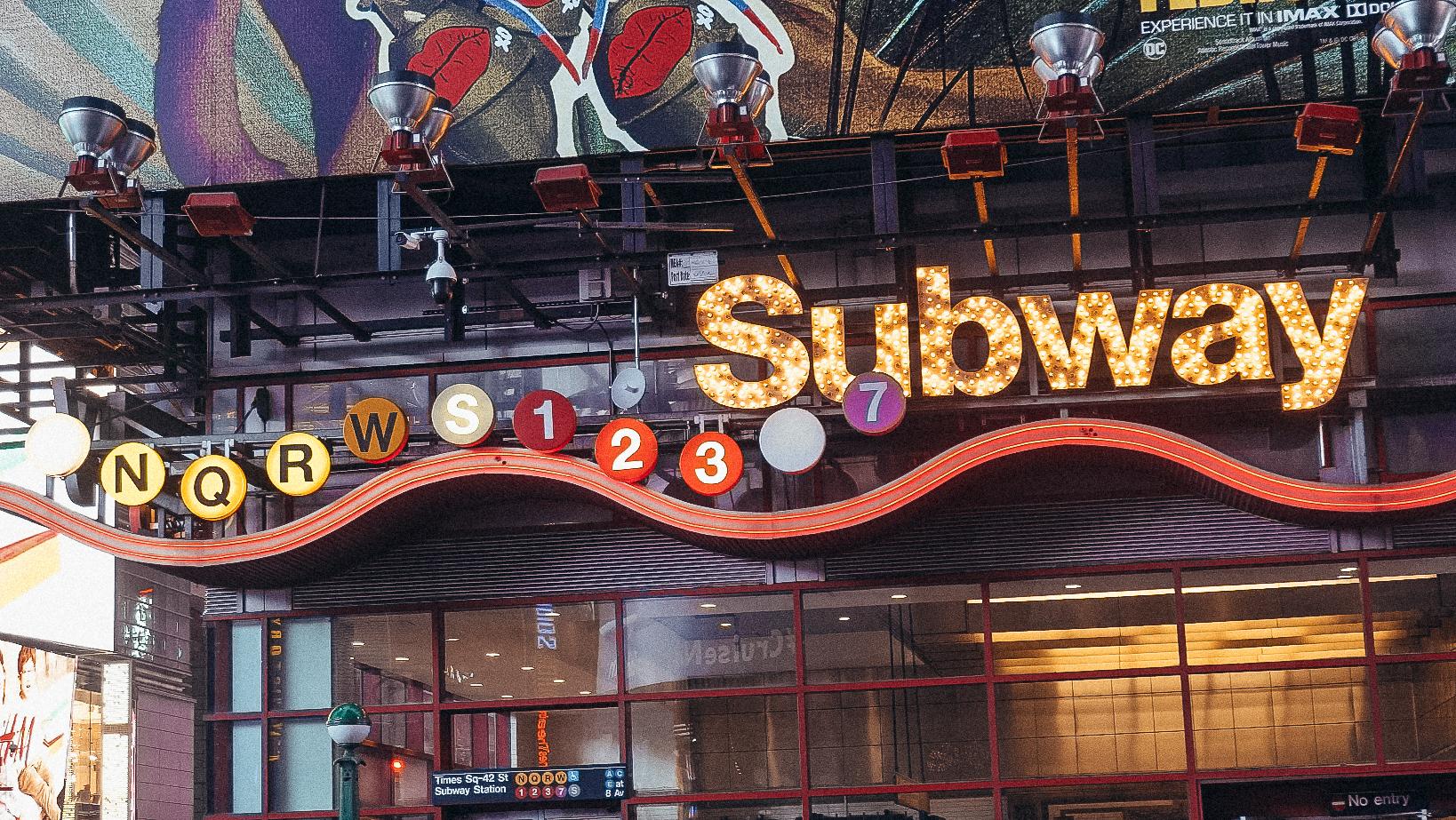 Foto da placa iluminada na entrada do metrô de Nova York