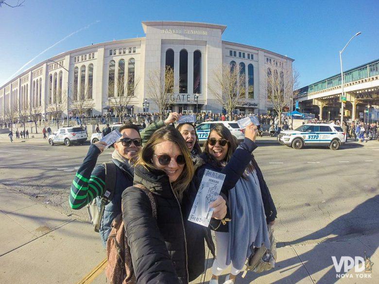 Foto da Bia com os amigos segurando os ingressos em frente ao estádio dos Yankees
