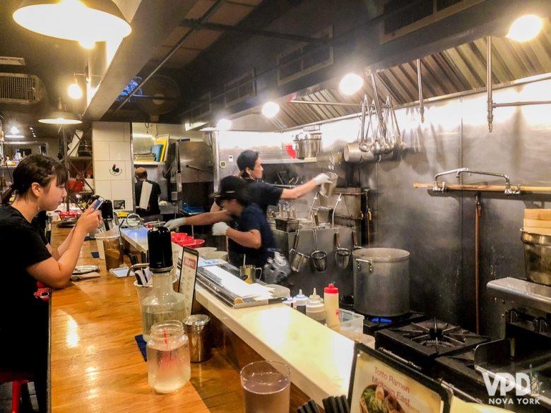 Foto do balcão do restaurante, com os chefs preparando a comida atrás - também uma opção para sentar em dupla ou sozinho.