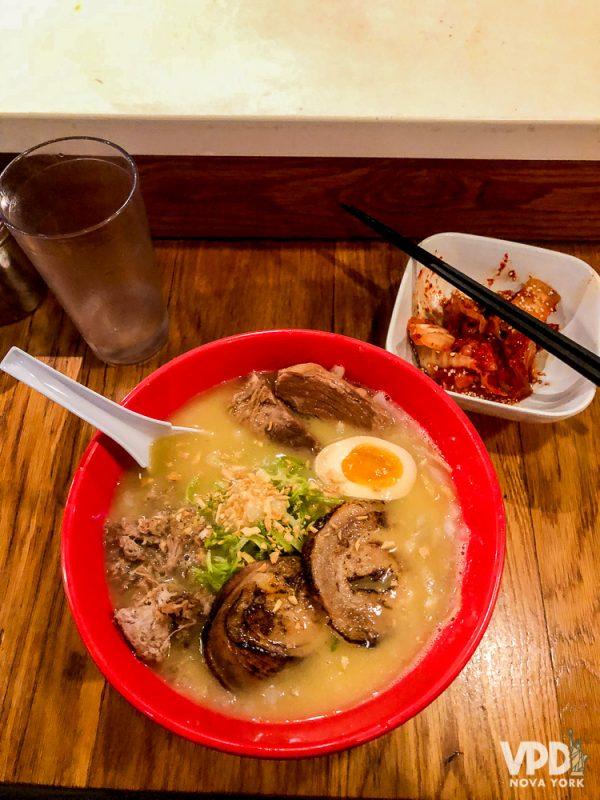Foto da tigela de ramen do Totto Ramen, em Nova York, com a entrada de kimchi ao lado