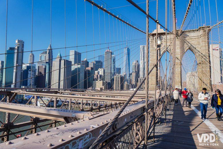 Foto da Brooklyn Bridge, com o céu azul e prédios ao fundo.