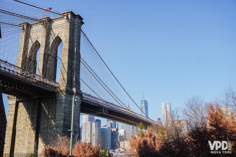 Foto da Brooklyn Bridge, com o céu azul e prédios ao fundo e as folhas do outono ao redor.