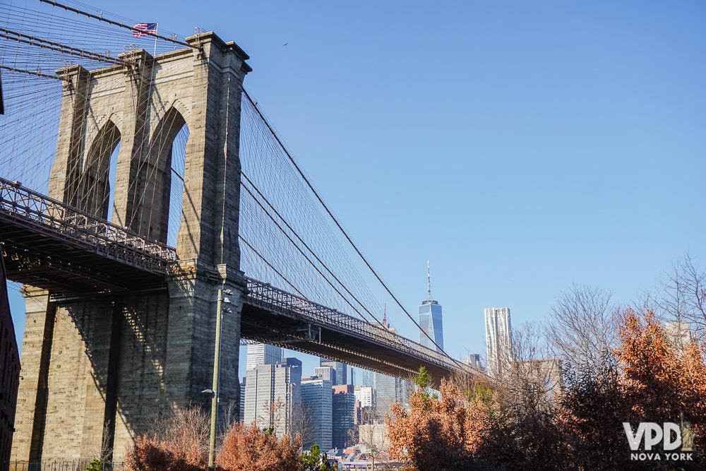 Foto da Brooklyn Bridge em Nova York, com o céu azul ao fundo.