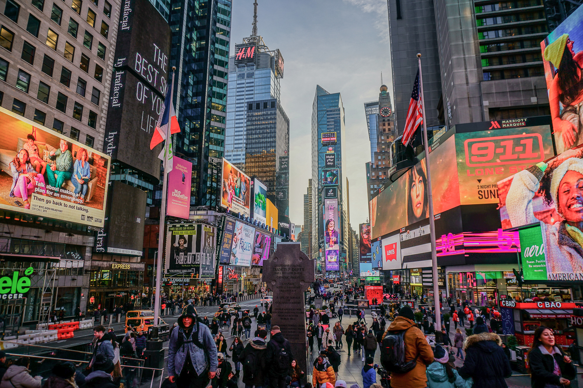 Foto da Times Square iluminada e cheia ao entardecer, com os prédios de Nova York ao fundo