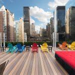 Foto da varandinha no telhado do hotel The Pod 51 em Nova York, com cadeiras coloridas para tomar sol, um sofazinho vermelho e os prédios da cidade ao fundo