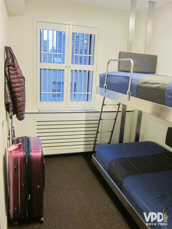 Foto do quarto do The Pod, com uma beliche e uma mala no canto