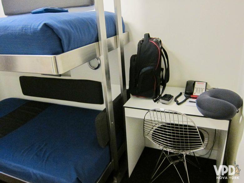 Espaço com uma cadeira, mesinha e telefone ao lado das beliches no The Pod 51