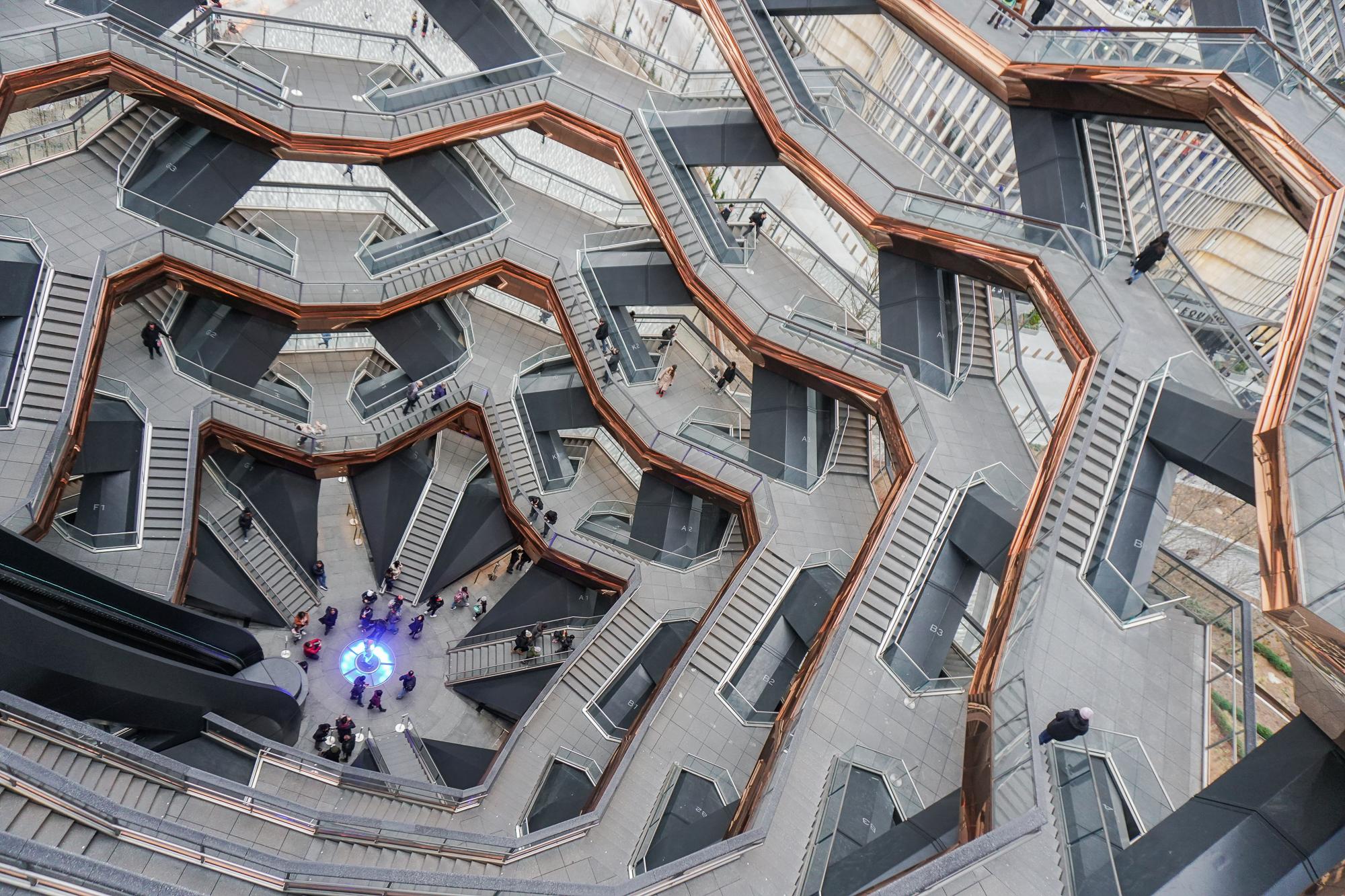 """Foto tirada de cima do The Vessel, mostrando as curvas da construção, com """"janelas"""" de vidro por toda sua extensão"""