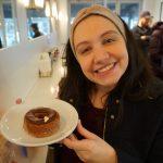 Foto da Renata segurando um prato com um cronut e sorrindo - uma das muitas opções de comida boa em Nova York.