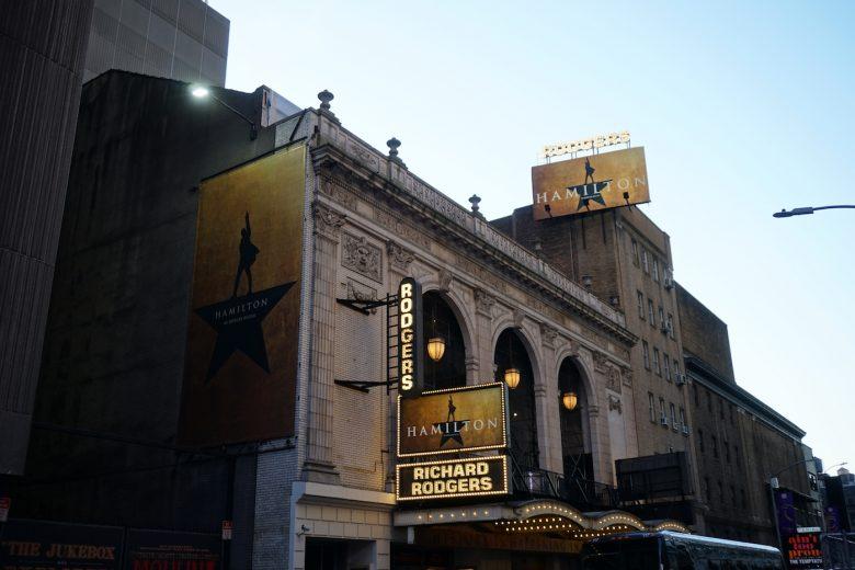 Foto da fachada da Broadway em Nova York, com cartazes do musical Hamilton em três pontos diferentes