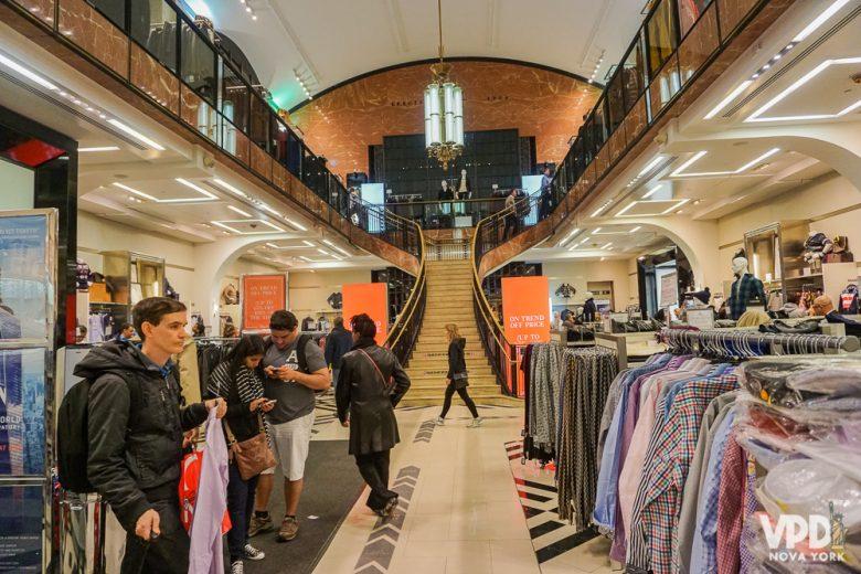 Foto da seção de roupas da loja Century 21, com uma ampla escadaria mais ao fundo