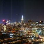 Foto da cidade de Nova York iluminada à noite, com o céu escuro ao fundo