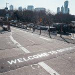 """Foto de um escrito que diz """"Welcome to Brooklyn"""" no chão da rua, com os prédios e o céu de Nova York ao fundo"""