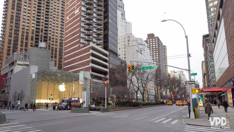 Importante dar preferência sempre para as lojas oficiais da Apple para comprar iphone. Foto de uma rua com a loja da Apple à direita, com a maçã iluminada no vidro