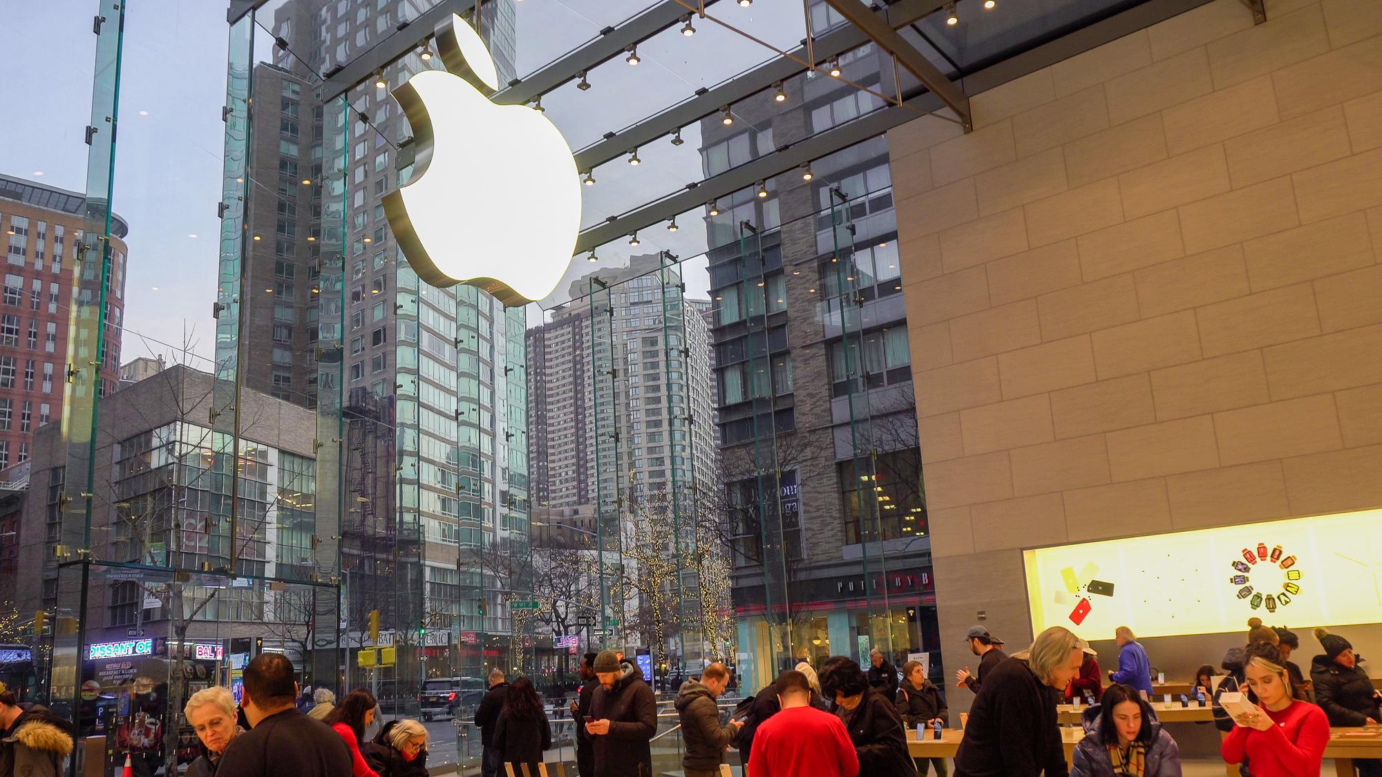 Foto de uma loja da Apple em Nova York, cheia de pessoas e com a maçã que é o logo em tamanho gigante sobre o vidro
