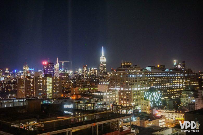 Foto da cidade de Nova York iluminada à noite, com o Empire State em destaque no fundo.