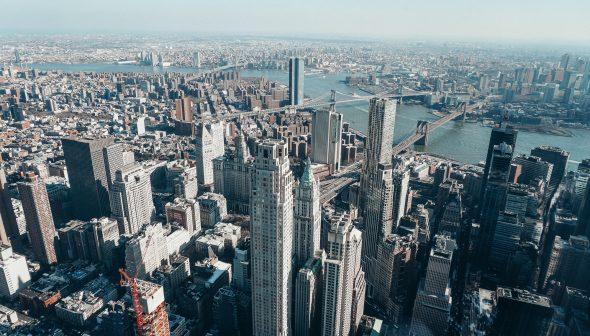 Foto da cidade de Nova York durante o da, com os edifícios altos e o céu claro ao fundo.