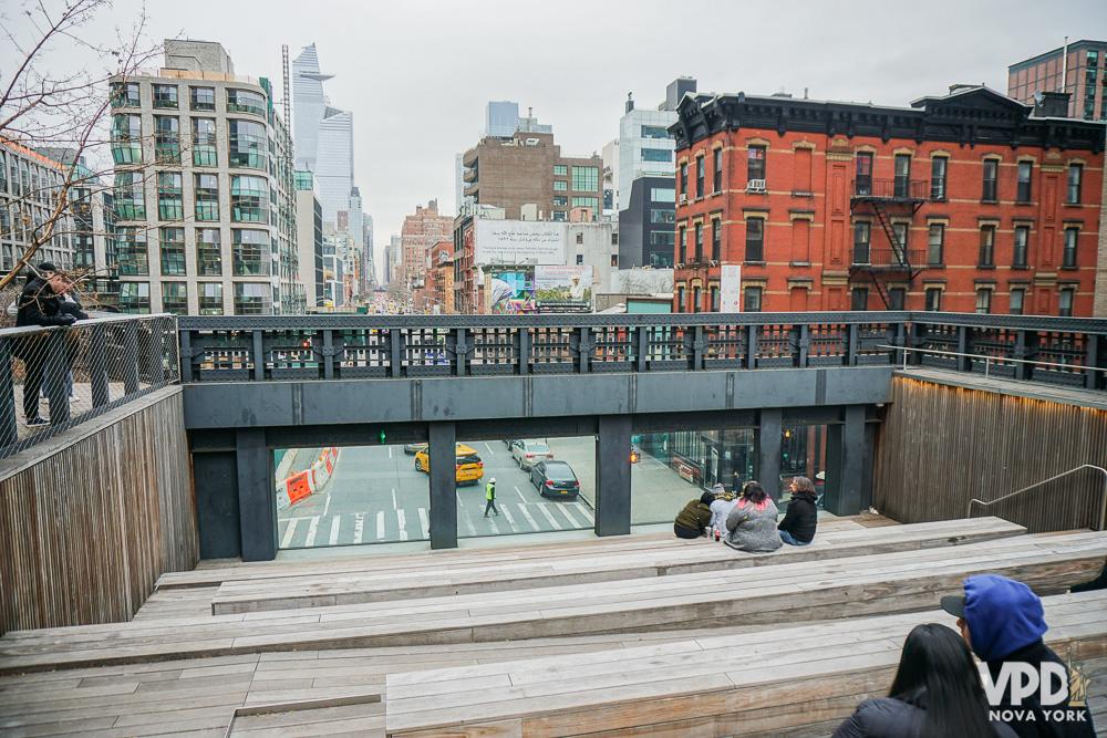 Foto de pessoas sentadas em uma plataforma de madeira no The High Line, com a cidade ao fundo