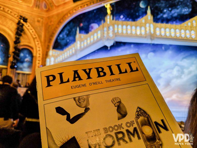 Imagem de uma playbill, o programa dos musicais da Broadway. Ele está sendo segurado acima do palco, e a capa indica que se trata do musical The Book of Mormon. A Broadway Week acontece em fevereiro e é uma boa oportunidade de economizar.