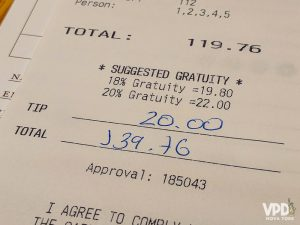Nota fiscal mostrando o valor total de 139,76 e uma gorjeta de 20 dólares.