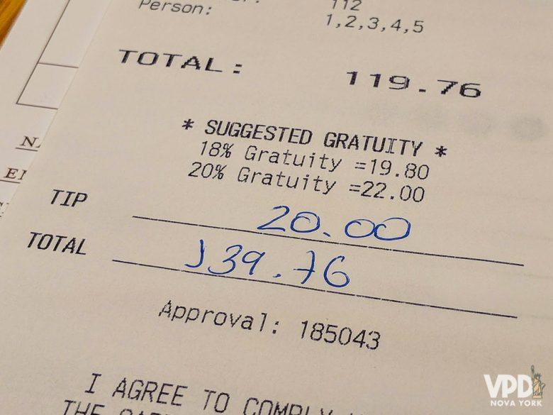Conta de restaurante em Nova York, com cobrança de taxa e gorjeta.