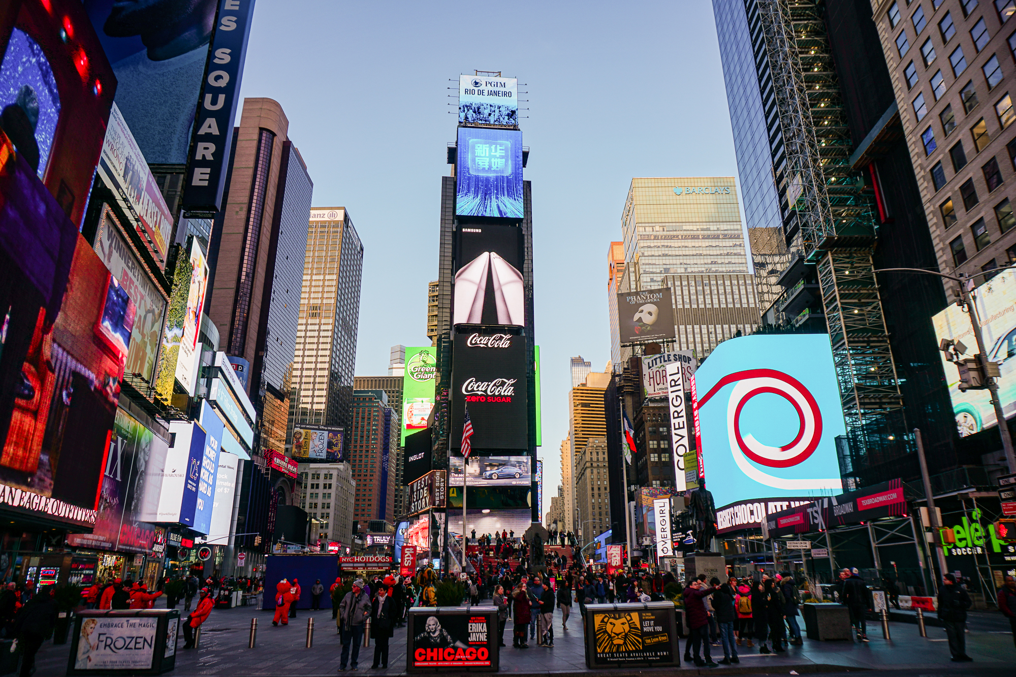 Foto da Times Square de Nova York durante o dia, com as lojas e os telões já começando a acender