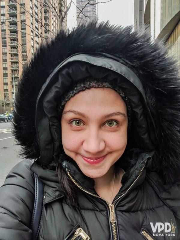 Foto da Renata com um casaco preto de frio bem quente, com pelinhos no capuz