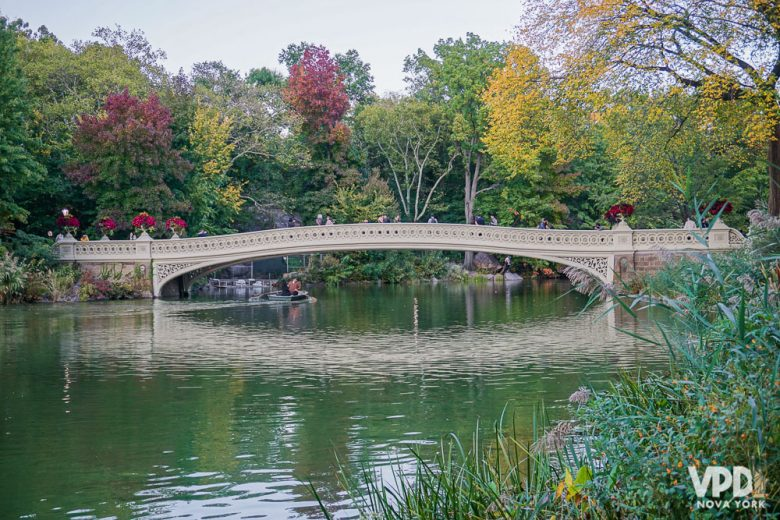 Foto da ponte do Central Park com árvores com folhas verdes, vermelhas e amarelas ao redor