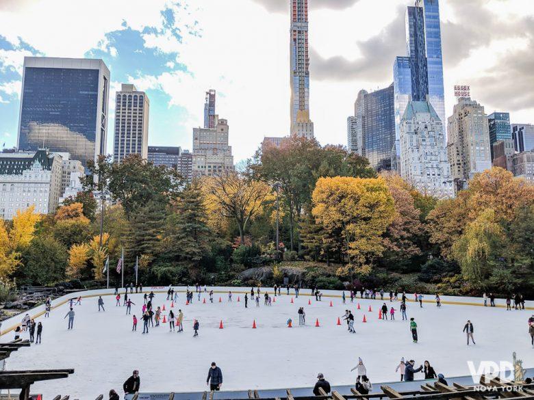 Foto do ringue de patinação do Rockefeller Center durante o dia, com árvores amareladas ao redor