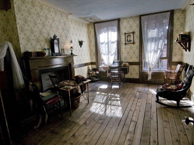 Foto do site do museu mostrando um dos cômodos com uma cadeira de balanço, uma mesinha, uma lareira e decoração