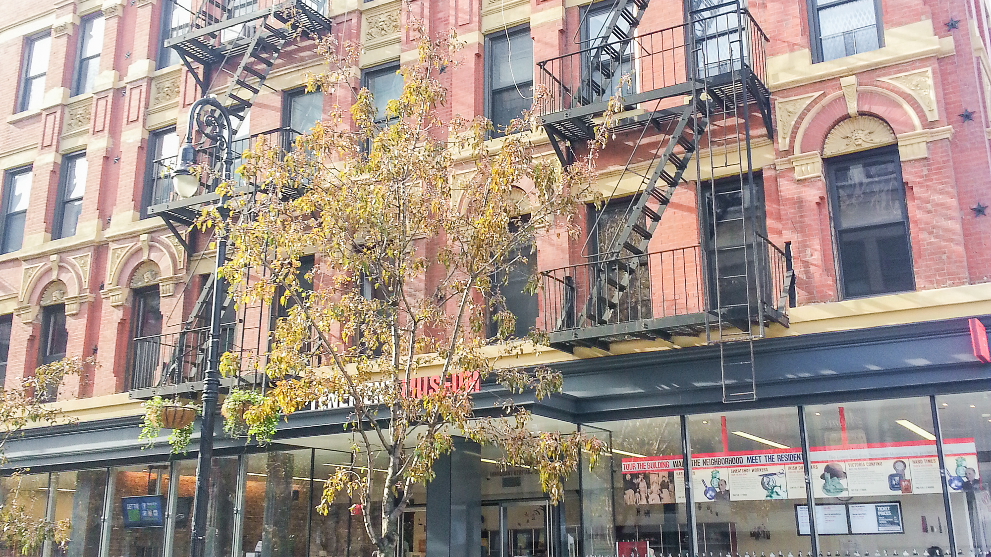 Fachada do prédio antigo onde fica o Tenement Museum em Nova York, com escadas de incêndio na frente e pintado de rosa