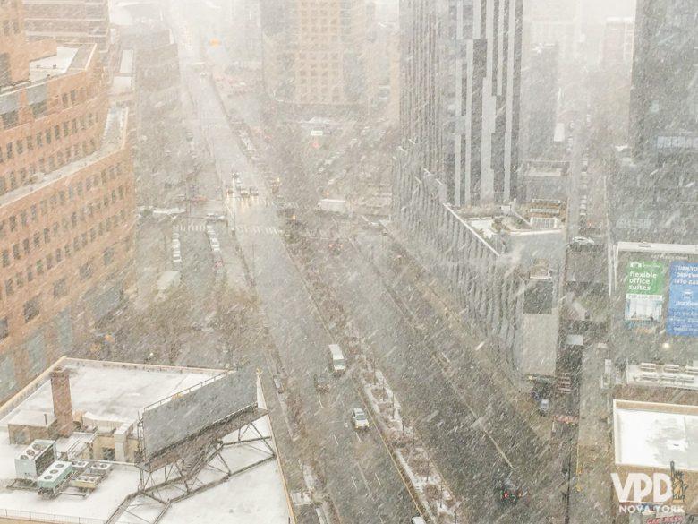 Foto da cidade de Nova York em janeiro, com muita neve caindo e acumulada nos telhados