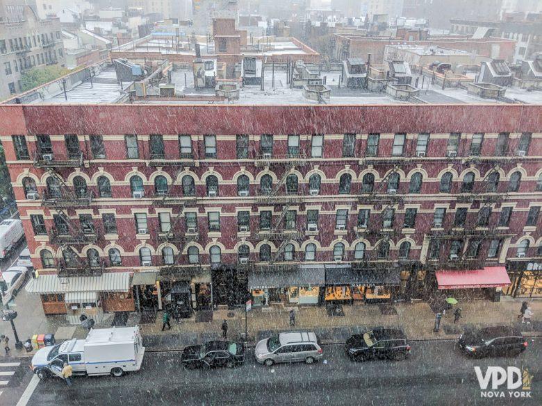 Foto de um prédio em Nova York com neve nos telhados e neve caindo do céu
