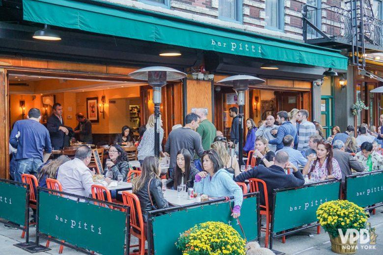 Foto de um restaurante com mesas cheias na calçada, durante o dia