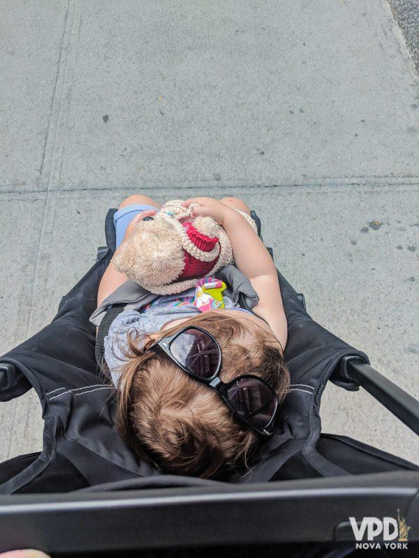 Foto da filha da Renata no carrinho, com óculos de sol na cabeça