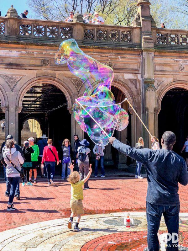 Foto de uma criança brincando com bolhas de sabão no Central Park