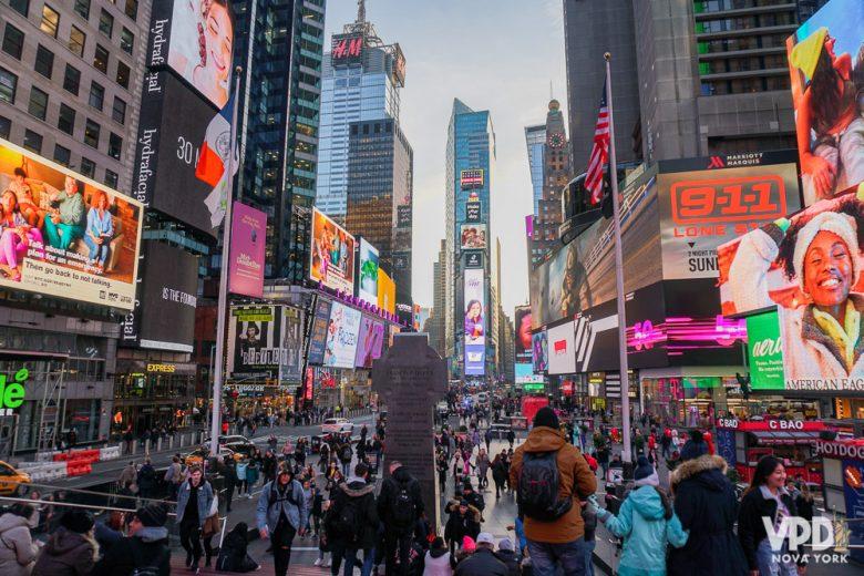 Foto da Times Square de Nova York durante o dia, com as lojas e os telões já começando a acender. Os personagens da Times Square são medonhos para adultos e mais ainda pra crianças