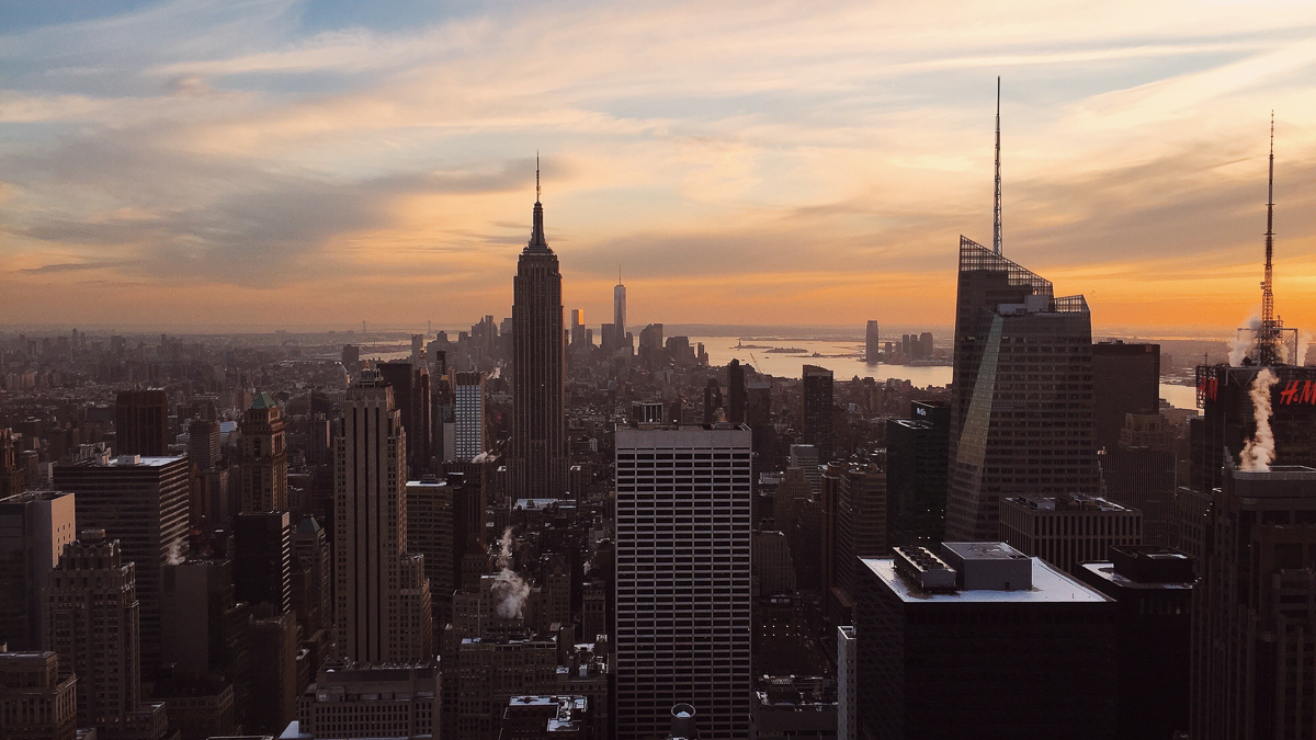 Foto da cidade de Nova York no pôr do sol, com os prédios escuros e o céu azul, rosa e laranja