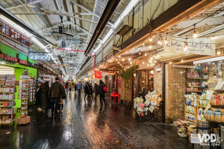 Foto do Chelsea Market, com estabelecimentos dos dois lados e iluminação de Natal