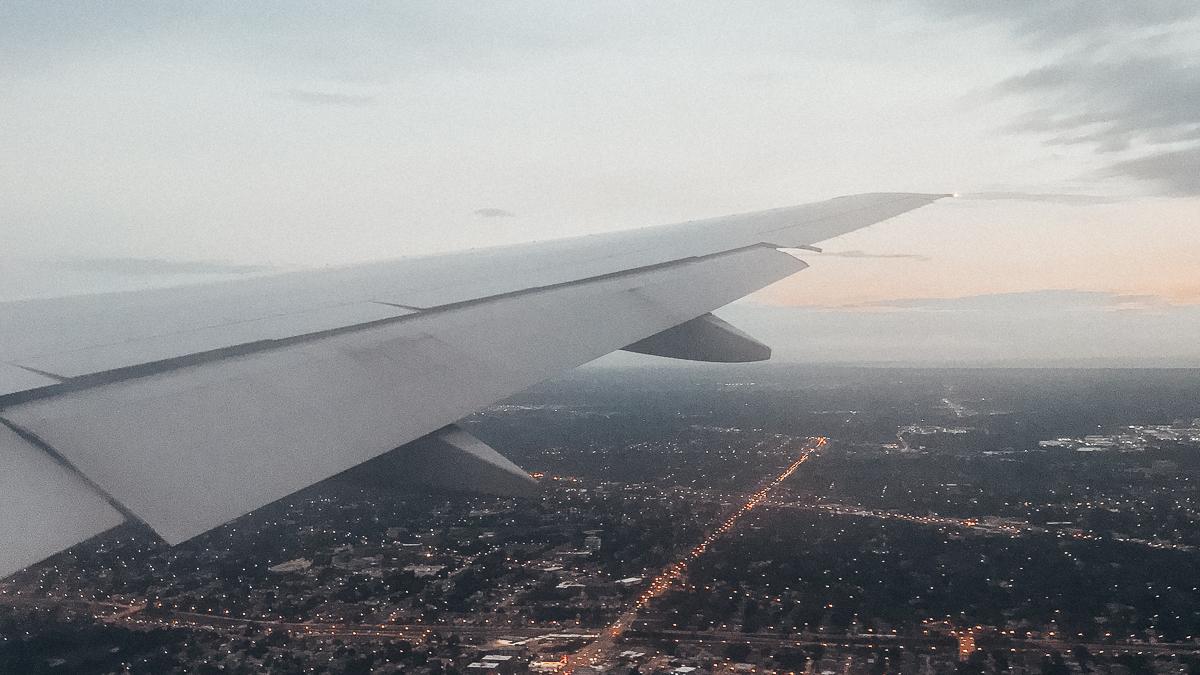 Foto da asa de um avião sobrevoando a cidade de Nova York, com um céu cinza-claro ao fundo