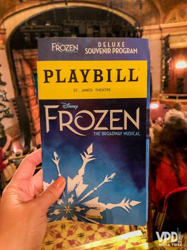 Imagem de um playbill, uma revistinha que traz informações dos musicais da Broadway. Nesse caso ele é do musical Frozen e está sendo segurado dentro do teatro.