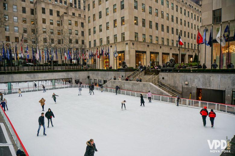Pista de patinação no Rockfeller Center, onde algumas pessoas estão patinando. Essas pistas funcionam em janeiro!