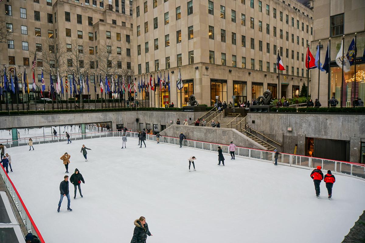Imagem da pista de patinação do Rockfeller Center. Há pessoas patinando e bandeiras e prédios ao redor.